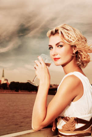 Beautiful blond girl drinks champagne near the river photo