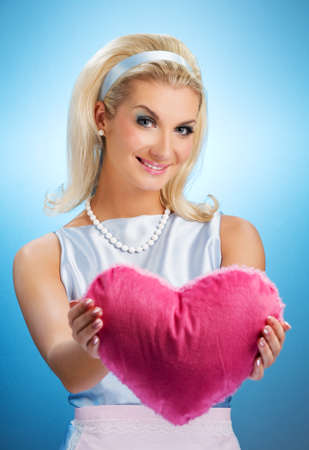 Beautiful young woman with heart pillow photo