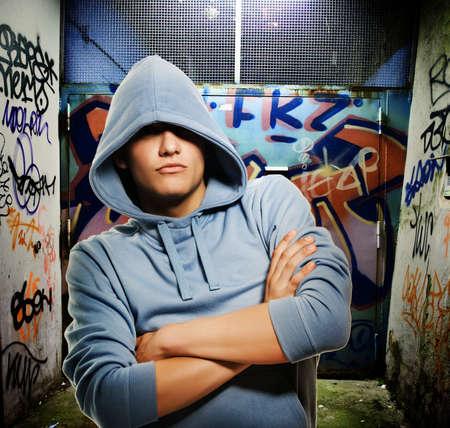 de maras: Hooligan fresco buscando un graffiti pintado en la puerta de enlace