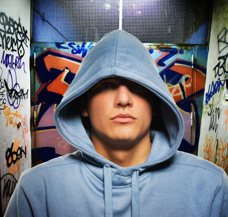 aggressive: Cool looking hooligan in a graffiti painted gateway