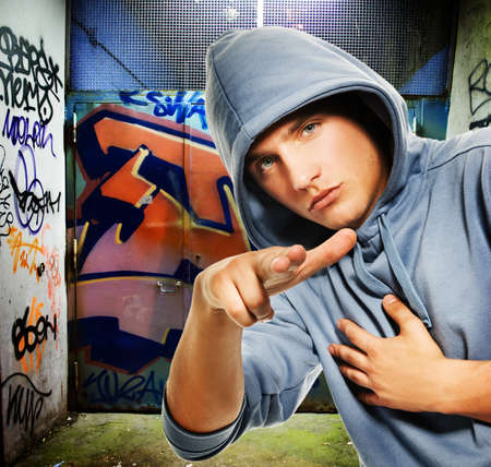 pandilleros: Hooligan fresco buscando un graffiti pintado en la puerta de enlace