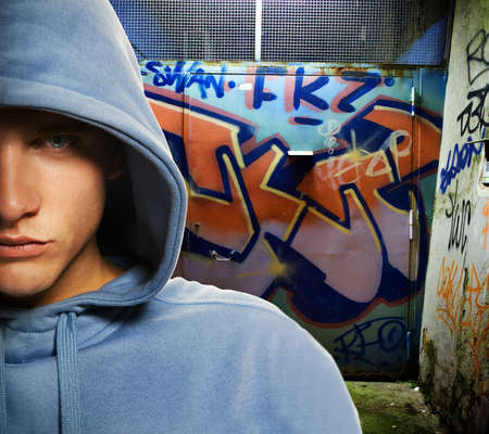 Cool looking hooligan in a graffiti painted gateway photo