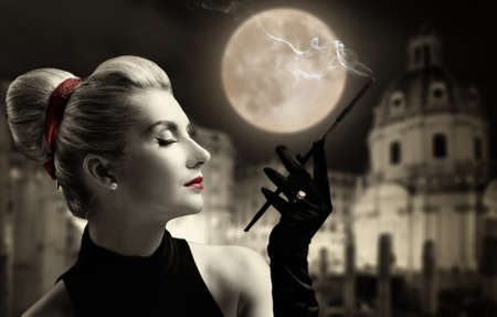 noir: Beautiful young lady smoking. Old city behind her. Stock Photo