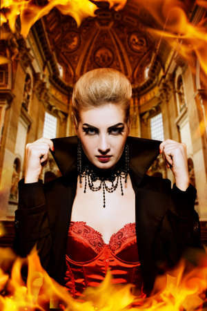 Female vampire in a burning church photo