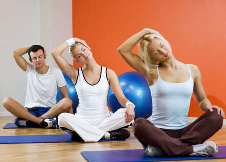 Group of people doing yoga exercise (focus on woman in the middle) Stock Photo - 4410730