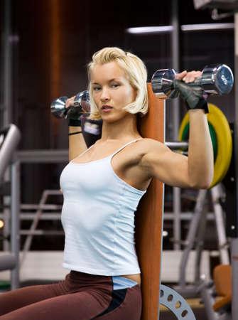 Strong beautiful woman lifting heavy dumbbells