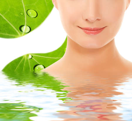 Beautiful young woman over green leaf background reflected in water