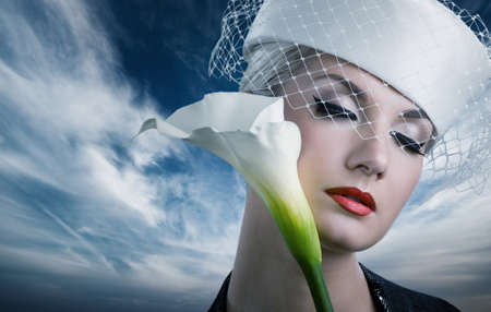 Beautiful young woman with white kala flower photo