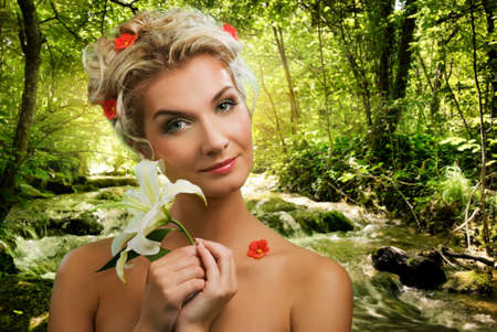 Beautiful young woman with lily in forest photo