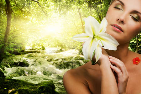 Beautiful young woman with flower in forest Stock Photo
