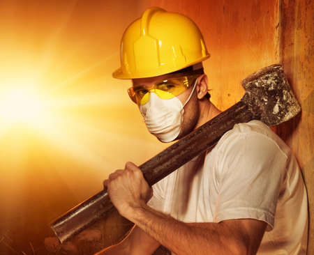 Builder with big metal hammer Stock Photo
