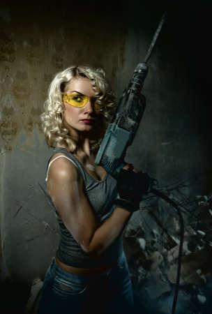 mujer con pistola: Hermosa mujer rubia con grandes taladro en sus manos