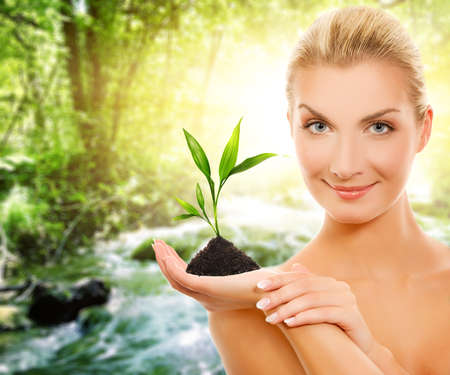 Beautiful woman with young plant in forest Stock Photo - 4519776