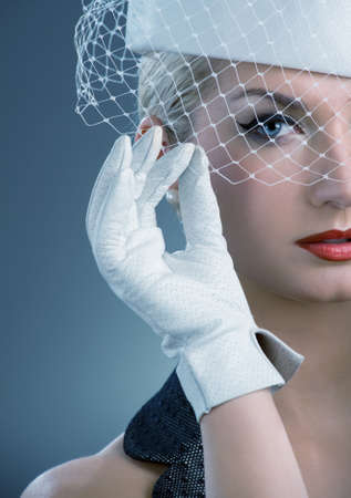 Beautiful young woman in white hat with net veil. Retro portrait