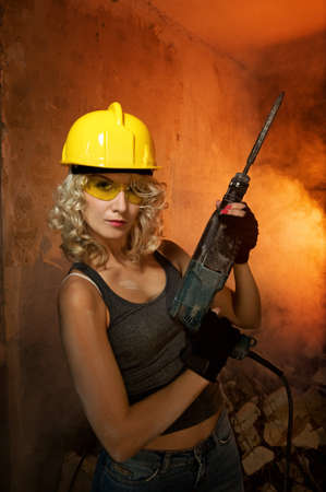 Beautiful blond woman with heavy perforator in her hands photo