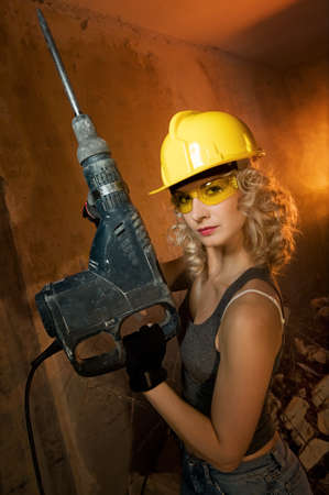 perforator: Beautiful blond woman with heavy perforator in her hands