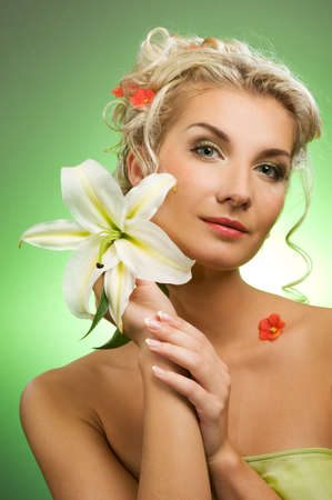 Beautiful young woman with lily flower. Close-up portrait photo