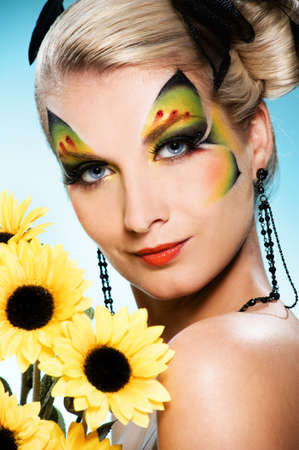 Young beauty with butterfly face-art and bouquet of sunflowers Stock Photo - 4561555