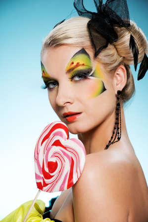 Young beauty with butterfly face-art heart shaped lollypop photo