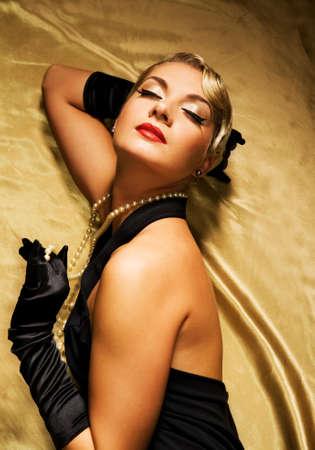 Lovely woman on golden fabric retro portrait photo