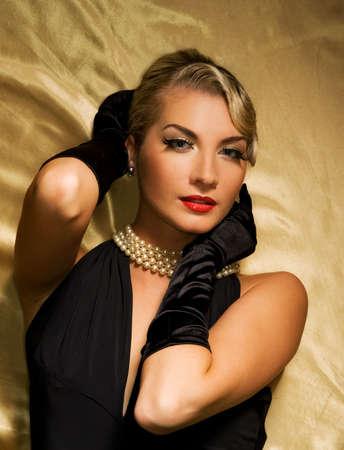 noir: Lovely woman on golden fabric retro portrait Stock Photo