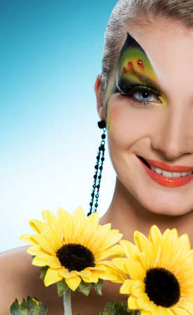 eyeshades: Young beauty with butterfly face-art and bouquet of sunflowers