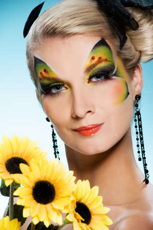 faceart: Young beauty with butterfly face-art and bouquet of sunflowers