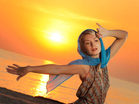 Romantic woman relaxing near the sea at sunset photo
