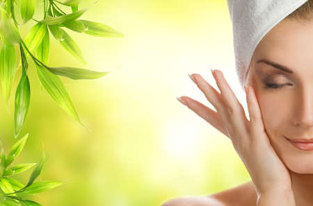 organic plants: Beautiful young woman applying organic cosmetics to her skin