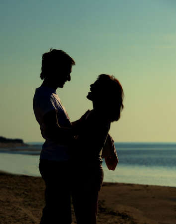 Man and woman in love near the ocean at sunset Stock Photo - 4790860