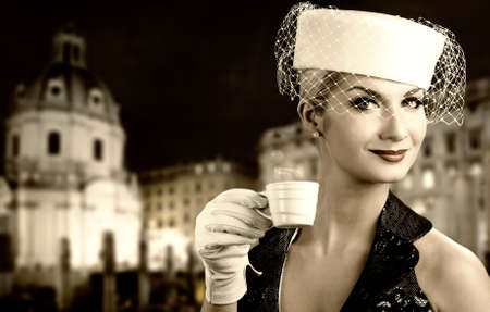 Beautiful young woman drinking coffee. Old city background behind her photo