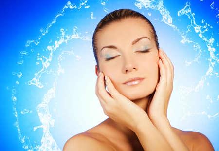 Beautiful young woman washing her face Stock Photo