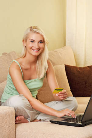 Happy young woman using credit card to make online purchase photo