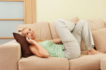 Happy young woman lying on sofa and talking on phone photo