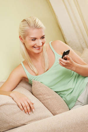 Happy young woman typing sms on mobile phone photo