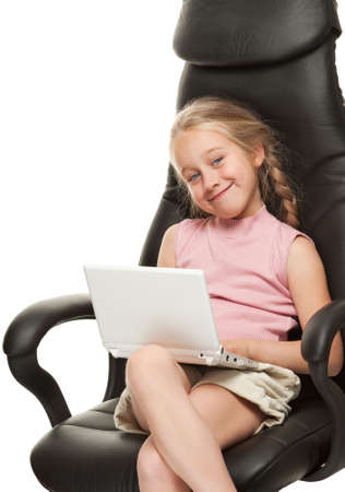 Pretty young girl with laptop sitting on a chair photo