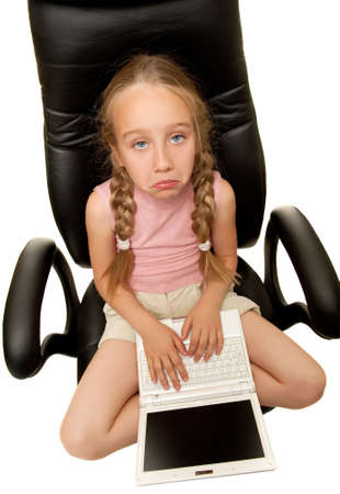 Sad young girl with laptop sitting on a chair photo