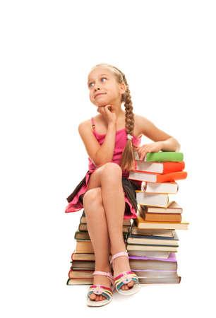 colegiala: Poco alumna sentada en una pila de libros Foto de archivo