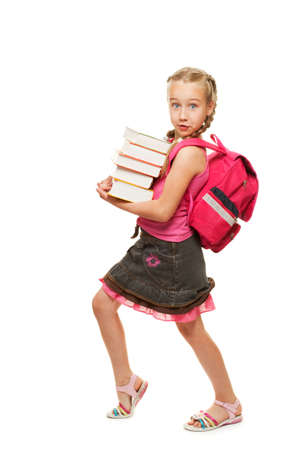 Happy litthe schoolgirl with a stack of heavy books photo