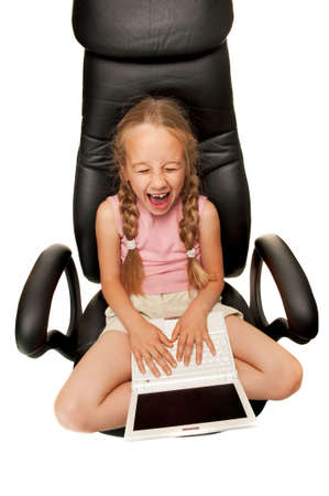 Funny young girl with laptop sitting on a chair photo
