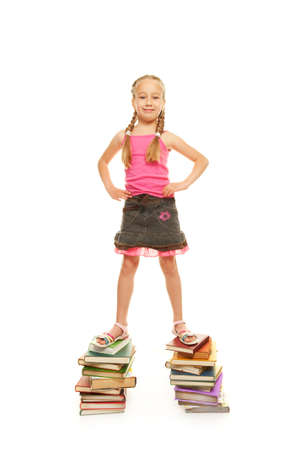 Funny schoolgirl standing on the books photo