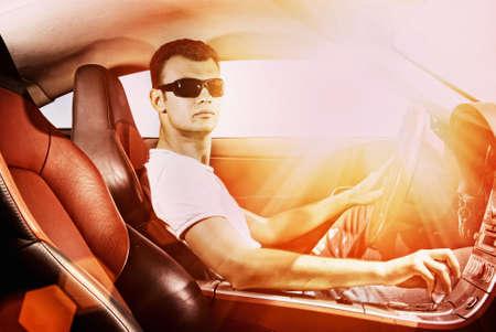 hombre conduciendo: Apuesto joven de conducci�n deporte moderno autom�vil Foto de archivo