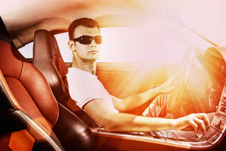 Handsome young man driving modern sport car photo