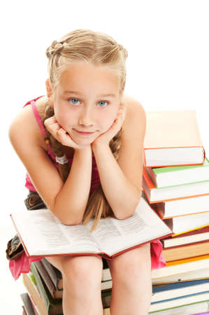 Thoughtful little schoolgirl sitting on a stack of books     photo