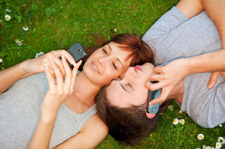 Young couple with mobile phones outdoor     photo