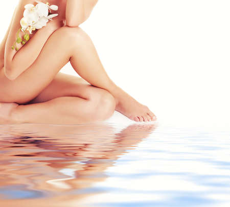 Female legs with white orchid Stock Photo - 5172013