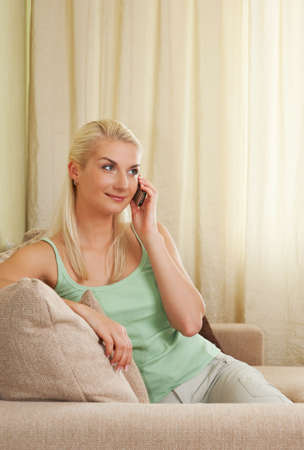 Happy young woman sitting on sofa and talking on phone     photo
