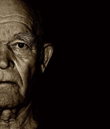 aging face: Elderly mans face over blask background