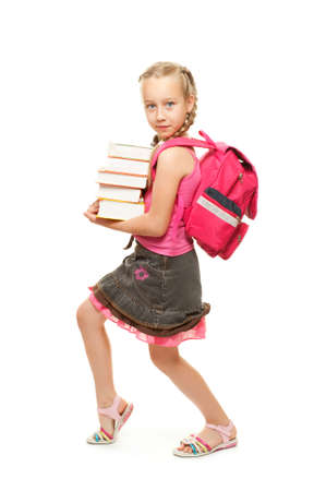 Happy little schoolgirl with a stack of heavy books Stock Photo - 5204880