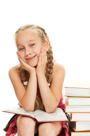 Happy little schoolgirl sitting on a stack of books     photo